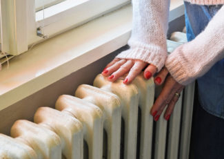 image of hands on radiator